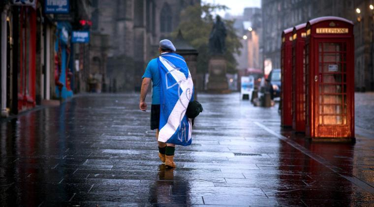 Un sostenitore dell'indipendenza scozzese cammina lungo una deserta via di Edimburgo dopo la diffusione dei risultati del referendum del 2014